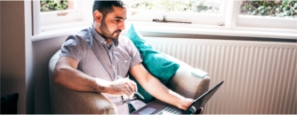 Arden University student on laptop sitting by window