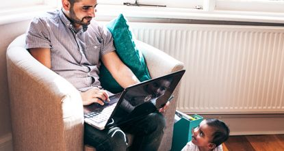 Man studying on a laptop while looking after a baby