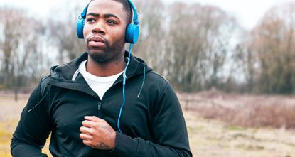 Man with headphones listens to a webinar while out running